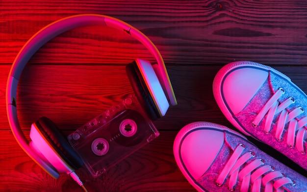 Stereo-kopfhörer mit audiokassette und turnschuhen auf holzoberfläche. neonrotes und blaues licht