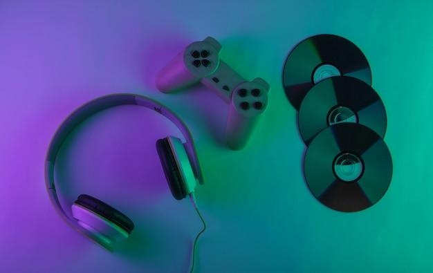 Stereo-kopfhörer mit retro-gamepad und cd-discs. neon lila und grünes licht. spielkonzept