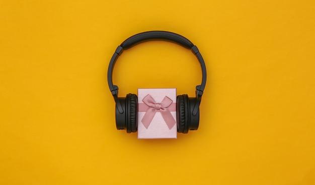 Stereo-kopfhörer und geschenkbox auf gelbem grund. musikliebhaber