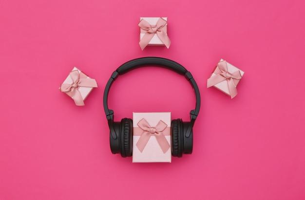 Stereo-kopfhörer und geschenkbox auf rosa hintergrund. musikliebhaber