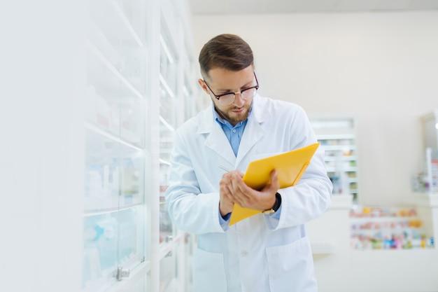 Steriler arbeitsplatz. kompetenter chemiker mit brille bei der arbeit mit dokumenten