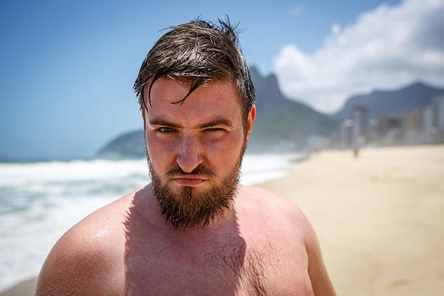 Stern bärtiger mann ohne hemd am strand.