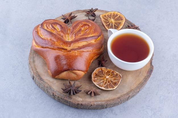 Sternanis getrocknete zitronenscheiben, eine tasse tee und ein süßes brötchen auf einem holzbrett auf marmoroberfläche