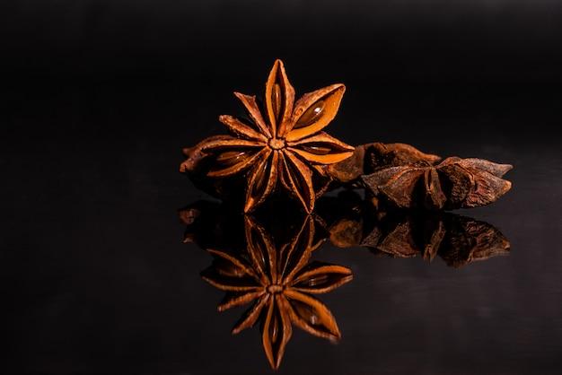 Sternanis vor einem dunklen hintergrund. gewürz auf einem glashintergrund mit reflexion