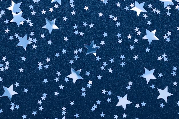 Sterne formen konfetti auf klassischer blauer farbe festlicher feiertagshintergrund glitzer funkelt.