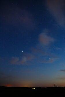 Sterne und wolken am himmel nach sonnenuntergang.