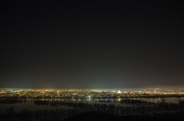 Sternenhimmel über der stadt und dem fluss während der frühjahrsflut. landschaft mit langer belichtungszeit.