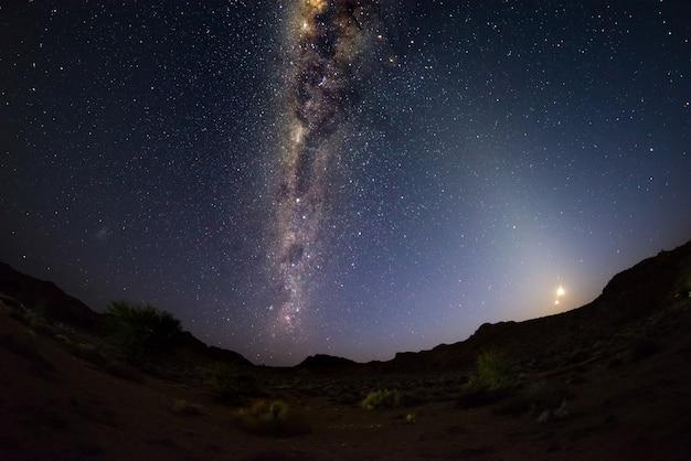 Sternenklarer himmel und milchstraße wölben sich mit dem steigenden mond, gefangen genommen von der namibischen wüste in namibia, afrika.