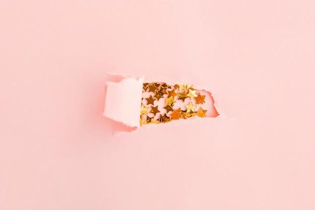 Sternenkonfettis auf rosa hintergrund unter heftigem hellrosa papier. weihnachtsferien-konzept.