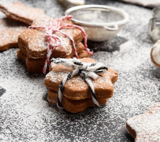 Sternförmig gebackene lebkuchenplätzchen mit puderzucker auf einem schwarzen tisch bestreut, nahaufnahme