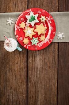 Sternförmige cookies auf einem roten teller und tasse mit sahne