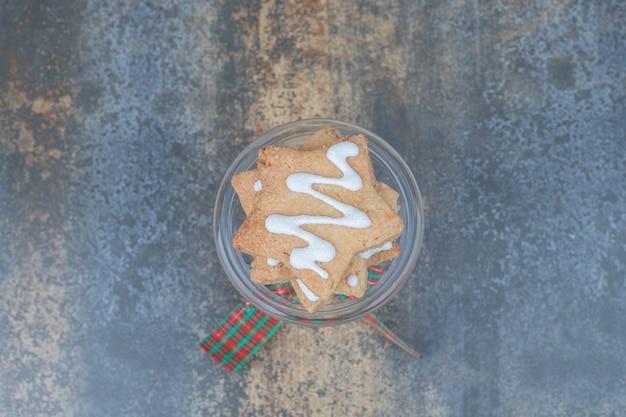Sternförmige lebkuchen auf glas verziert mit band. hochwertiges foto