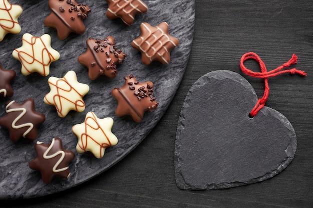 Sternförmige schokoladen auf dunkelgrauem steinbrett mit schwarzem herzen auf dunklem hintergrund