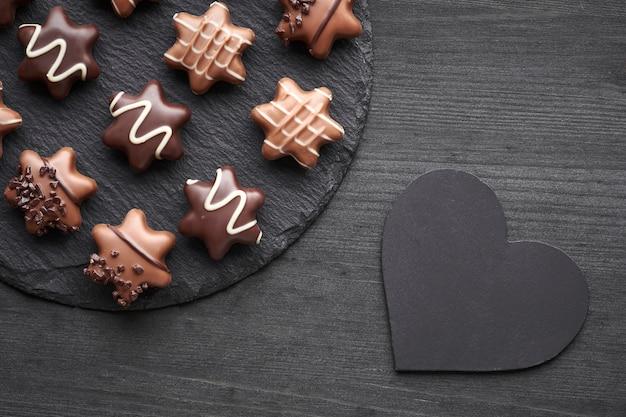 Sternförmige schokoladen auf dunklem strukturiertem hintergrund mit herzen