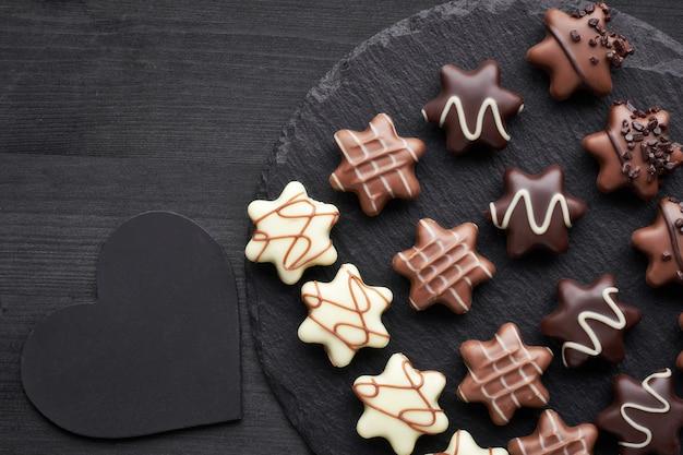 Sternförmige schokoladen auf dunklem strukturiertem hintergrund mit schwarzem herzen