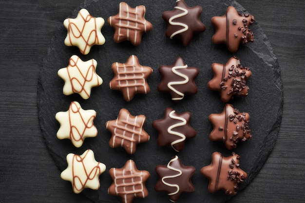 Sternförmige schokoladen auf dunklem strukturiertem hintergrund