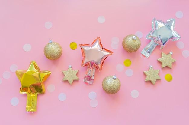 Sternfolienballons, weihnachtsschmuck und konfetty auf einem pastellrosa hintergrund