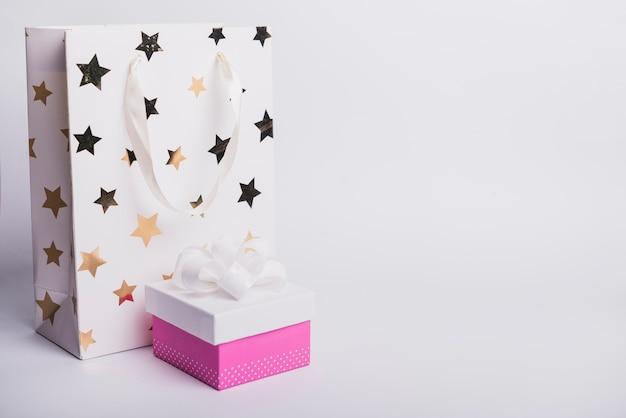 Sternform auf einkaufstasche mit der geschlossenen geschenkbox lokalisiert auf weißem hintergrund