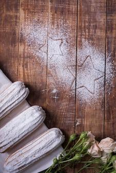 Sternform gezeichnet auf hölzernen schreibtisch mit gebackenen eclairs und rosen
