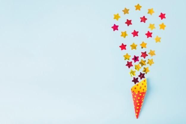 Sternform konfetti, die vom papierkegel mit tupfen auf blauem hintergrund herauskommt