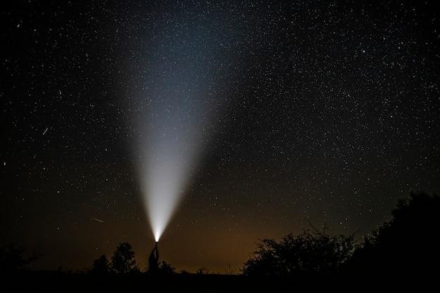 Sternschnuppen in der nähe einer taschenlampe, die von einem mann gehalten wurde