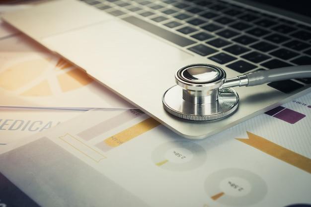 Stethoskop auf computer mit testergebnissen in doktor, der raumhintergrund und berichtsdiagramm für medizinisches konsultiert