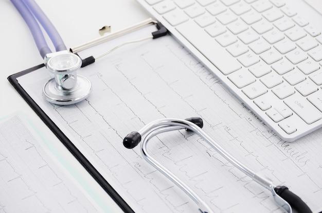 Stethoskop auf ecg papierdiagramm und laptop auf weißem hintergrund