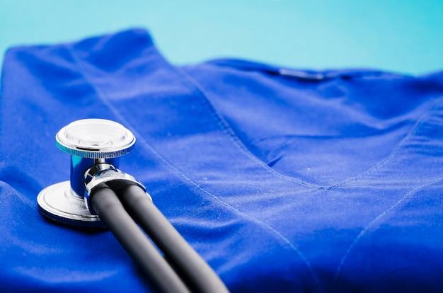 Stethoskop auf medizinischer uniform gegen blauen hintergrund