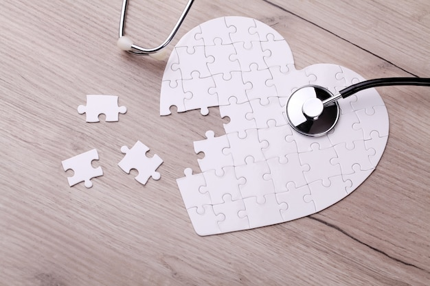 Stethoskop auf puzzle, das geheimnis der gesundheitsversorgung zu lösen