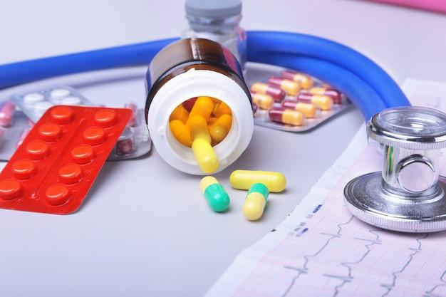 Stethoskop auf rx-rezept mit verschiedenen pillen liegen. gesundes leben oder versicherungskonzept.