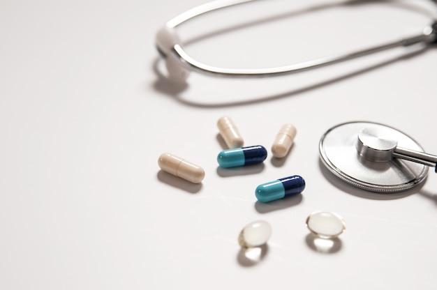 Stethoskop auf weißem hintergrund mit mix pillen isoliert