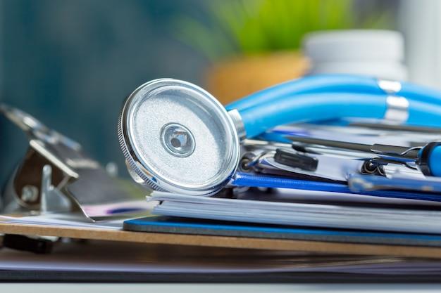 Stethoskop, das auf medizinischer form auf klemmbrett liegt.