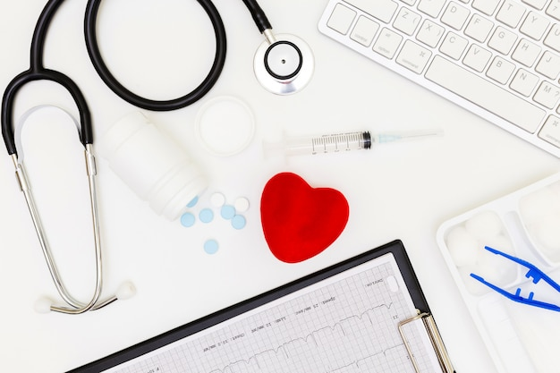 Stethoskop, draufsicht der schreibtischtabelle doktors, über ansichtdoktorarbeitswerkzeugen auf weißem, arztschreibtischkonzept.