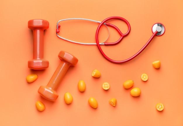 Stethoskop, frucht und hanteln auf farbigem hintergrund