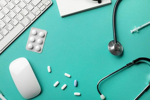 Stethoskop im doktorschreibtisch mit notizbuch, stift, tastatur, maus und pillen