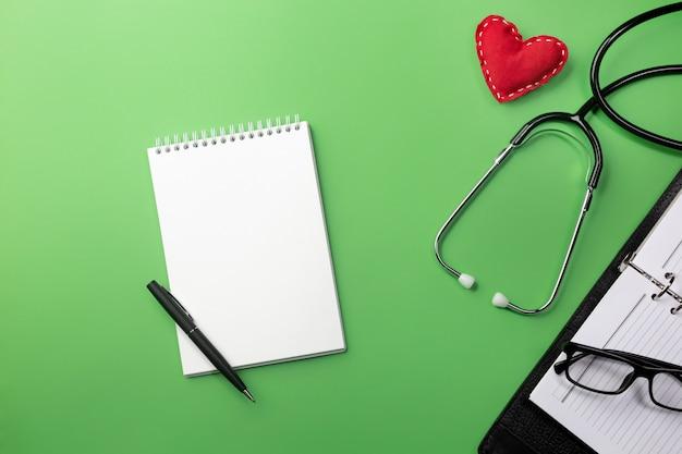 Stethoskop im doktorschreibtisch mit notizbuch und herzen