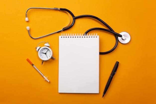 Stethoskop im doktorschreibtisch mit notizbuch, wecker und pillen
