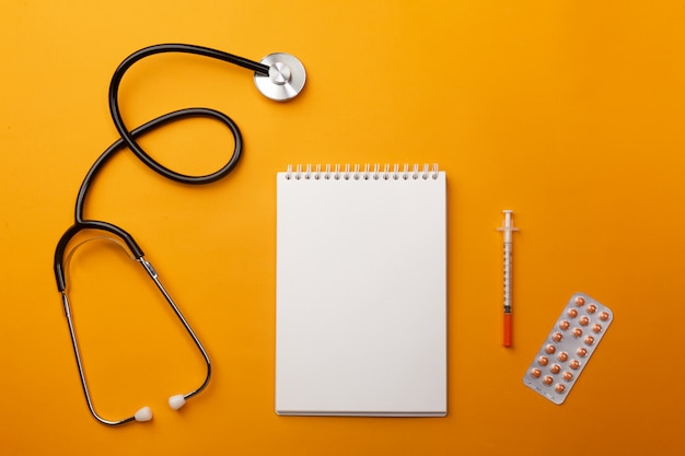 Stethoskop im doktorschreibtisch mit spritze und ampullen