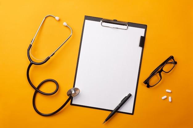 Stethoskop im doktorschreibtisch mit tablette, stift und pillen