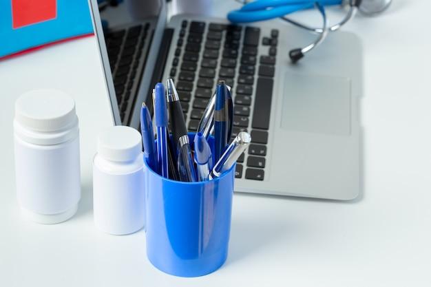 Stethoskop, laptop und pillen auf der weißen tabelle