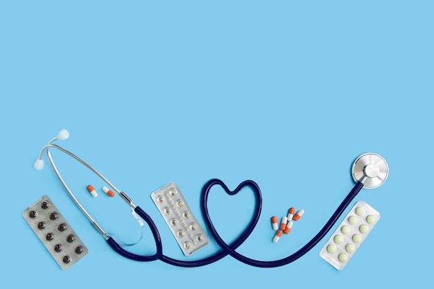 Stethoskop, medikamente auf blauem hintergrund mit kopierraum, draufsicht.