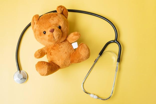 Stethoskop mit bärenpuppe auf gelbem hintergrund zur unterstützung des lebens und der krankheit von kindern. september aufklärungsmonat für kinderkrebs, gesundheits- und lebensversicherungskonzept