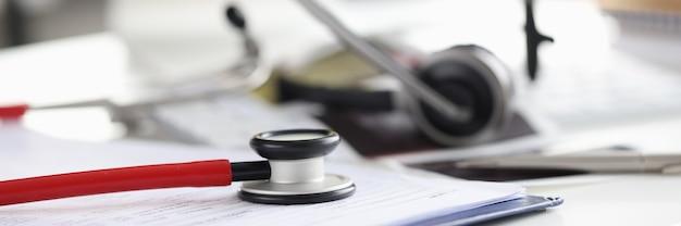 Stethoskop mit dokumenten und kopfhörer mit mikrofon auf dem desktop