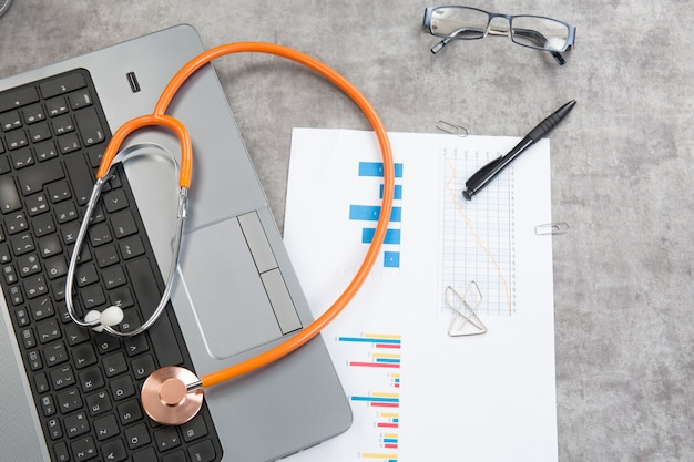 Stethoskop mit finanzdokumenten auf dem schreibtisch und einem laptop