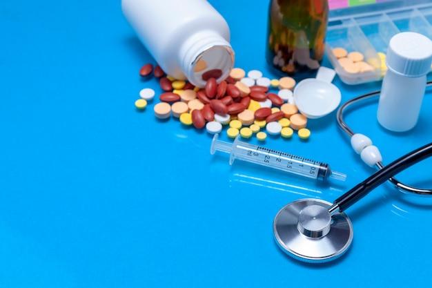 Stethoskop mit flasche medizin, fütterungsspritze, kapsel auf blauem hintergrund