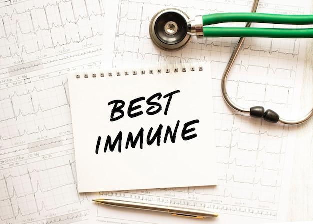 Stethoskop mit kardiogramm und notizblock mit text best immune. gesundheitskonzept.