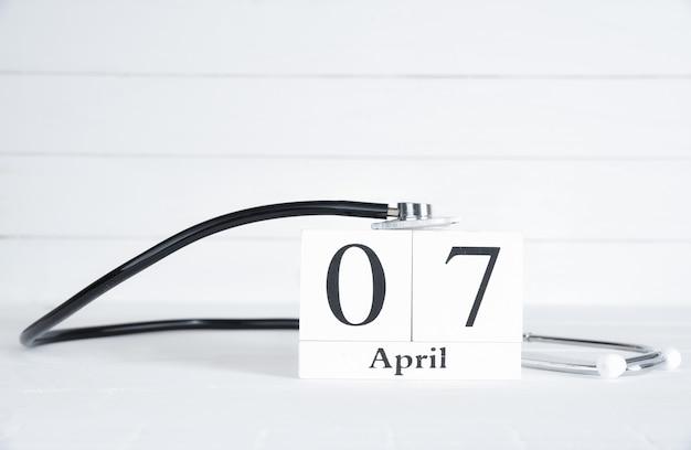 Stethoskop mit textholzklotzkalender am 7. april auf weißem hölzernem hintergrund.