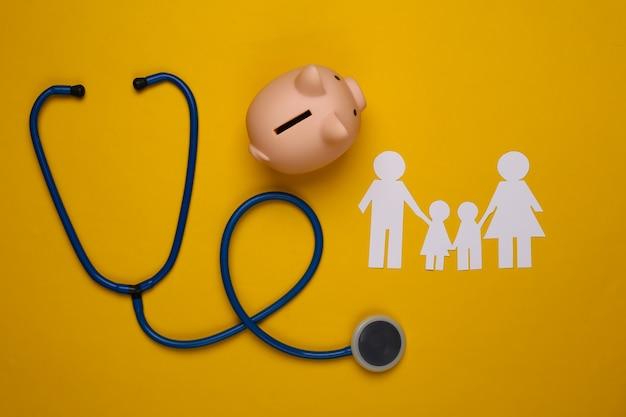 Stethoskop, papierkettenfamilie, sparschwein auf gelb, krankenversicherungskonzept