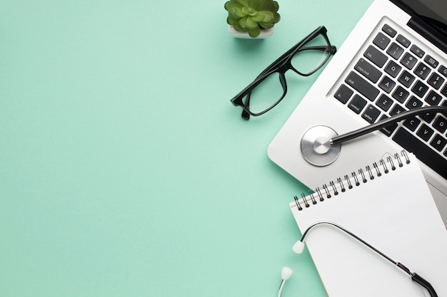 Stethoskop; spiral-tagebuch; spektakel und sukkulente mit laptop auf grünem hintergrund