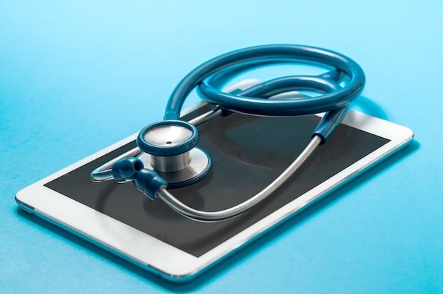 Stethoskop, tablet-pc auf blauem farbhintergrund